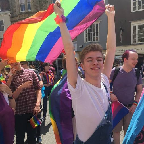 Jack is blonde and wearing a white t-shirt with blue dungarees. He smiles at the camera whilst waving a rainbow pride flag.